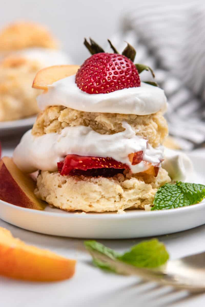 Shortcake stacked with peaches, whipped cream and fruit on top.