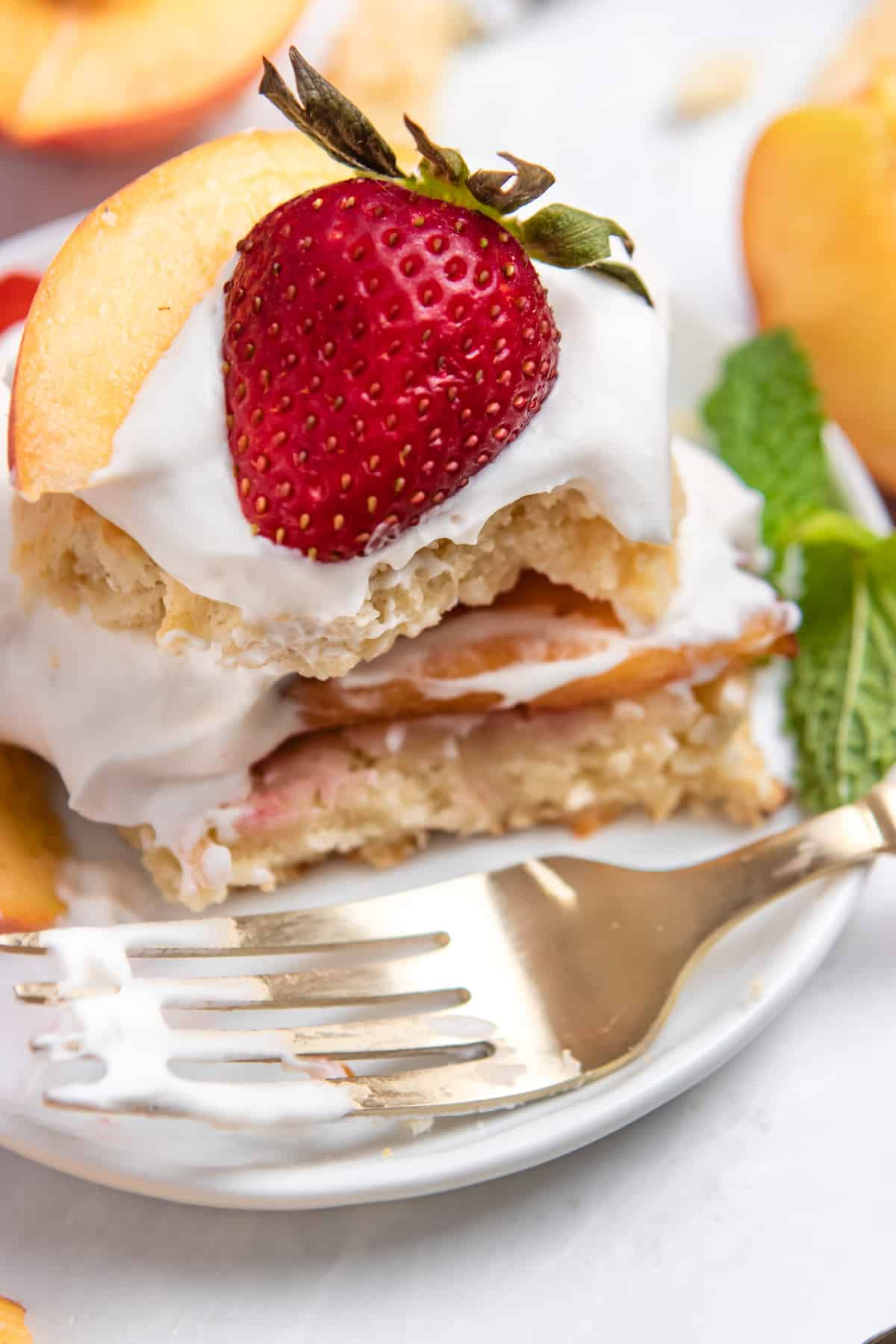 Fork on plate with slice cut out of strawberry peach shortcake.