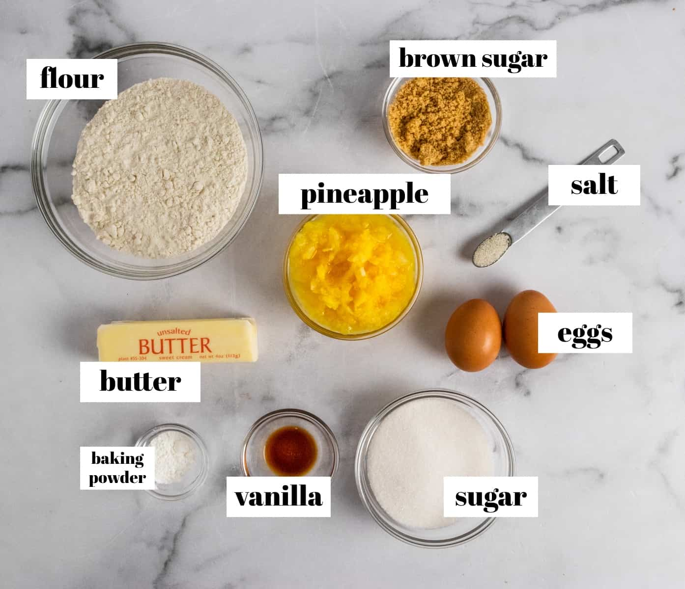 Flour, sugar, eggs, butter and other ingredients labeled on counter.