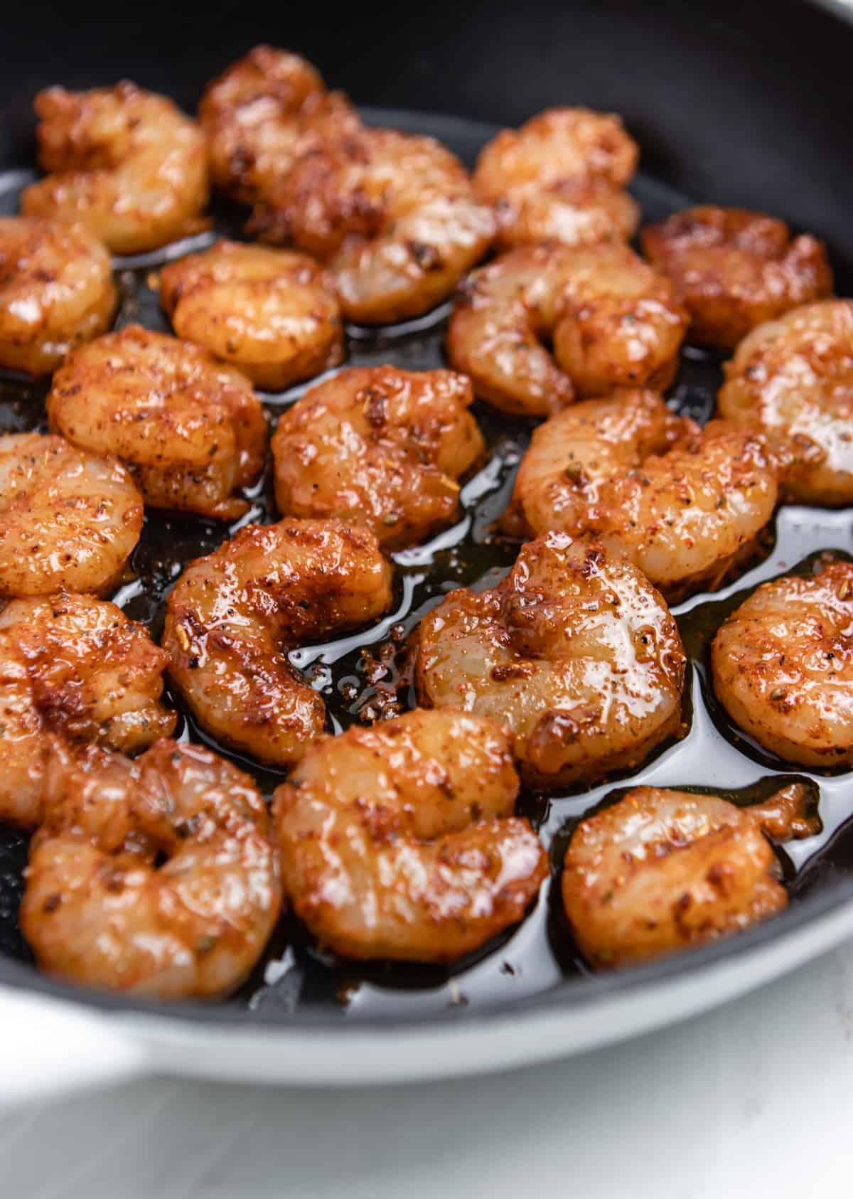 Spicy shrimp in skillet being pan fried.
