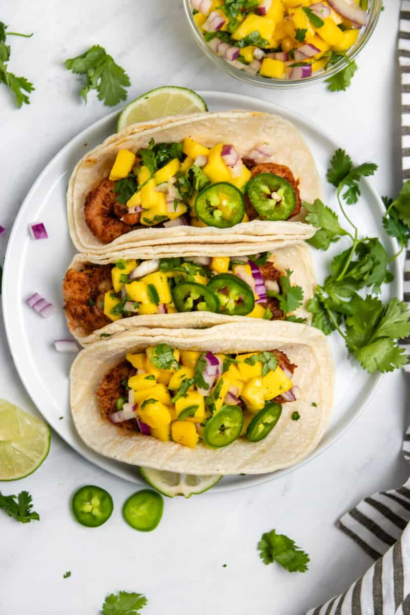 Overhead view of spicy shrimp tacos topped with mango salsa and fresh cilantro.
