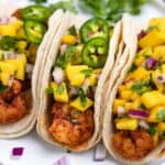 Spicy shrimp tacos on white plate topped with mango salsa and slices of jalepeño.