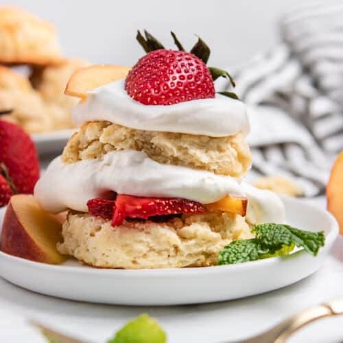 Peach Shortcake with fresh whipped cream on plate.