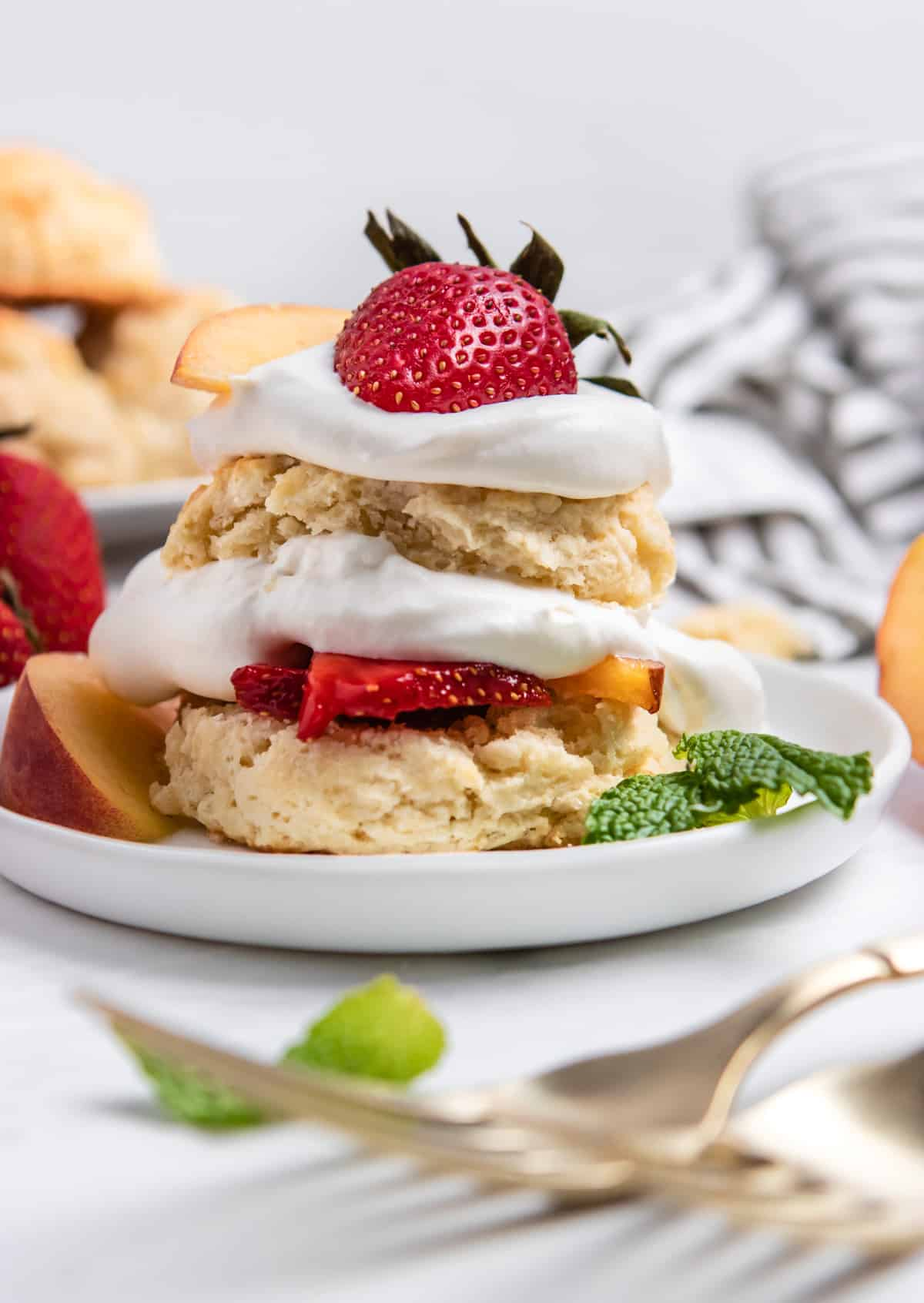 Strawberry peach shortcake on white plate with fresh mint and forks.