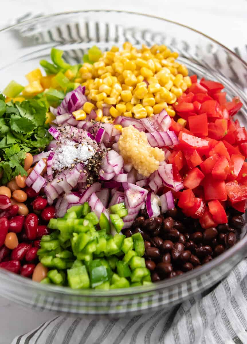 Peppers, tomatoes, beans, and more in mixing bowl.