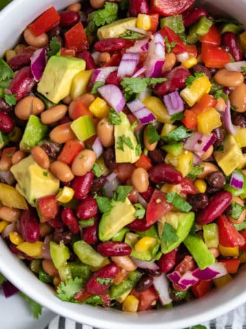 Overhead view of cowboy caviar dip with beans, avocado and more in bowl.