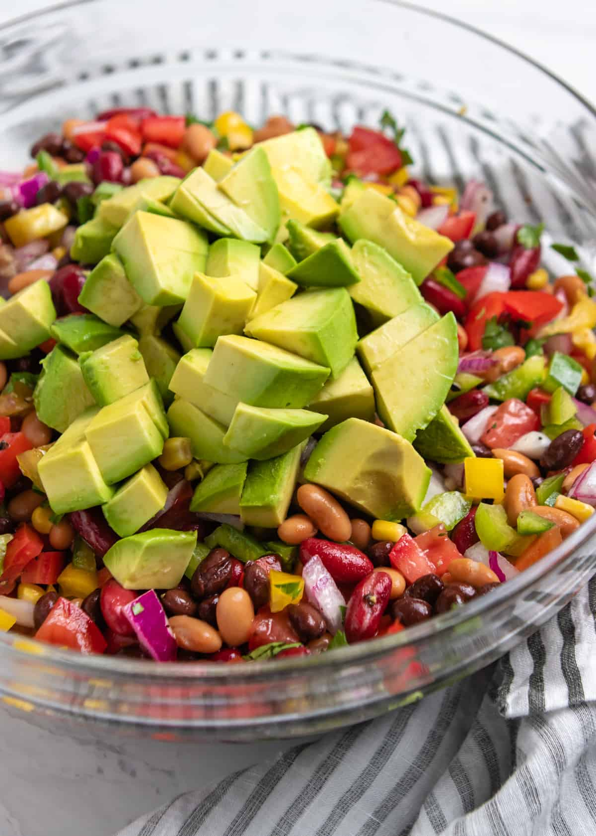 Cubed avocado on top of salad with beans, peppers and other ingredients.
