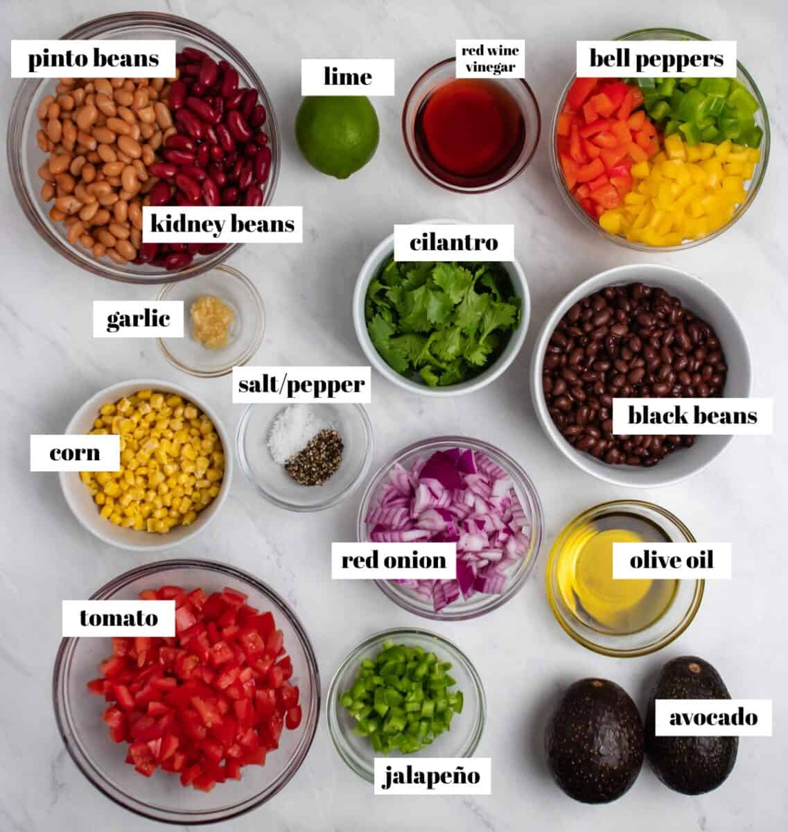 Peppers, beans, cilantro, avocado, corn and other ingredients labeled on counter.