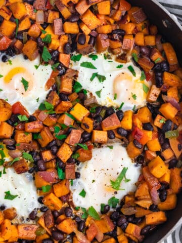 Sweet potato and black bean hash in skillet with eggs.