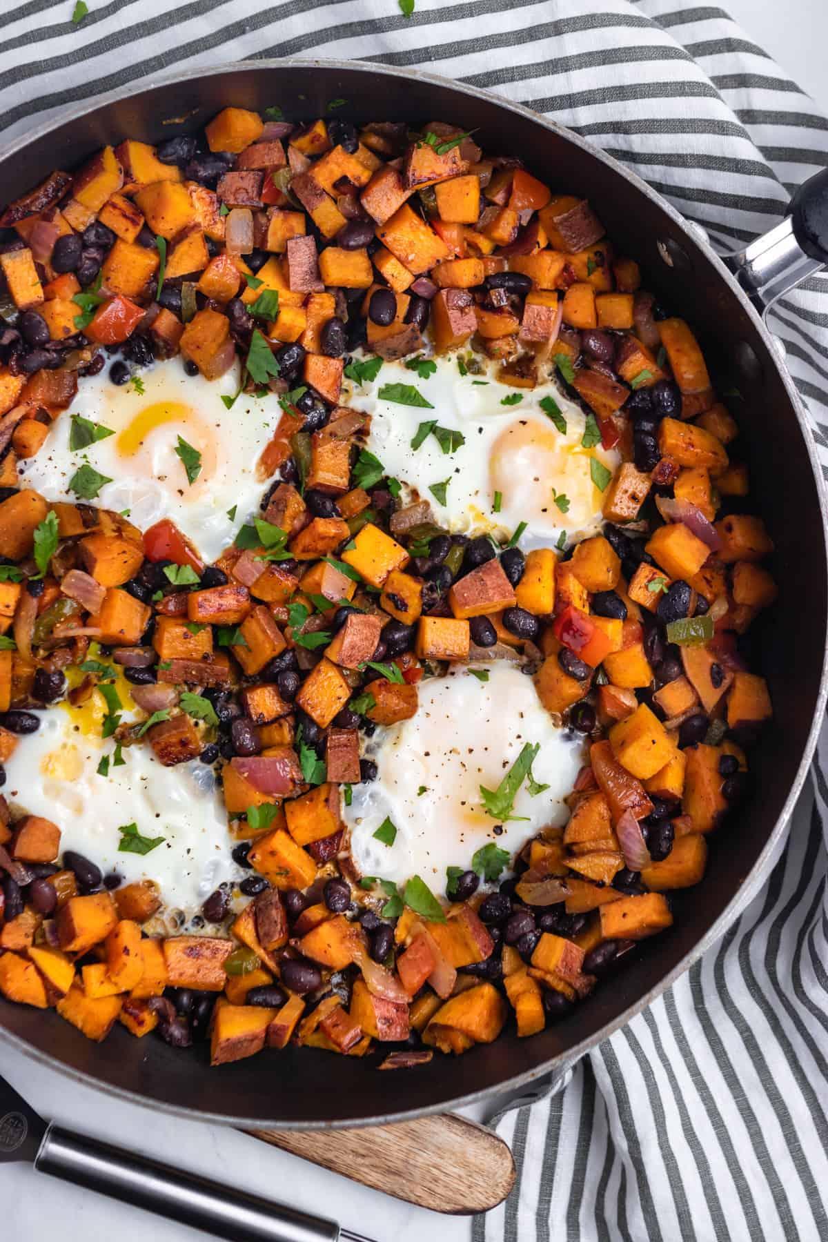 Frying pan with sweet potato hash and eggs.