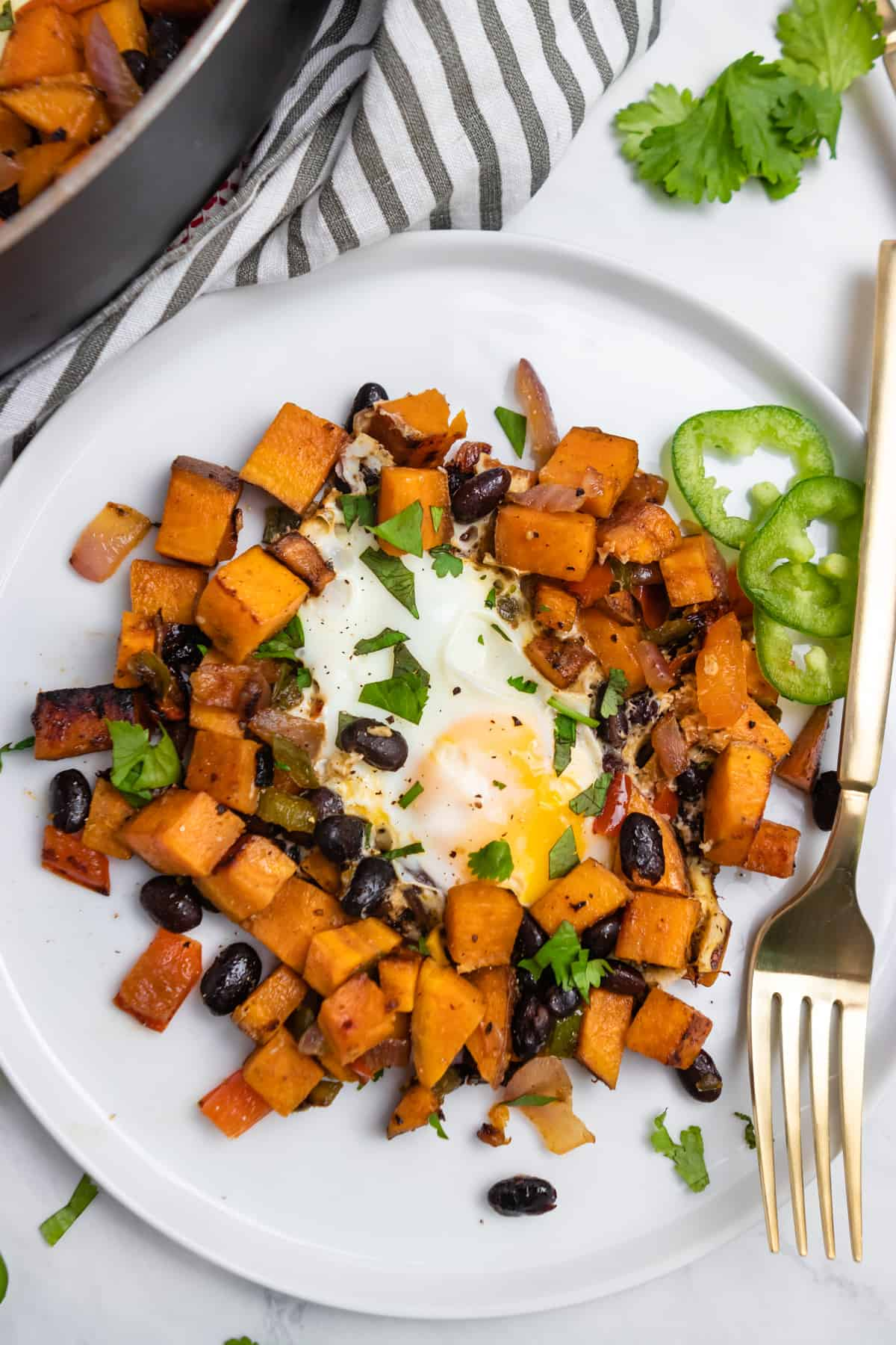 Sweet potato breakfast hash with black beans on plate with egg in center.