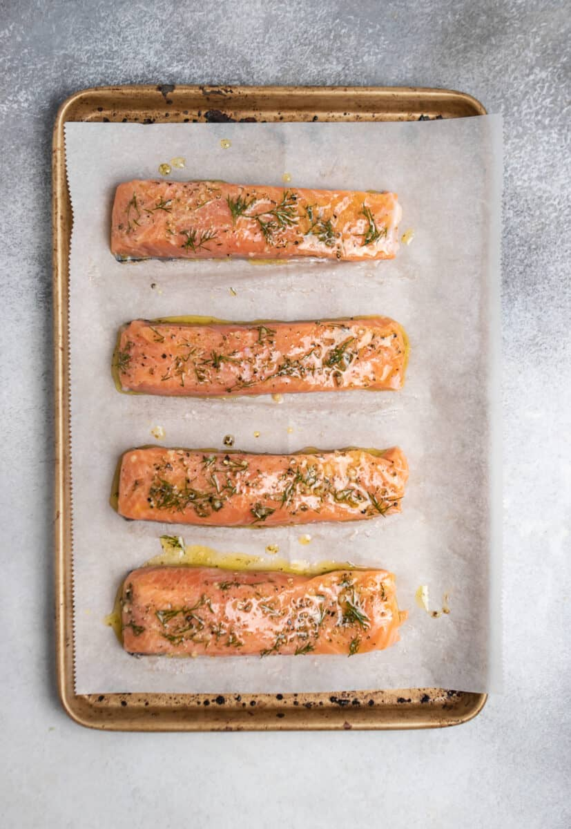 Salmon filets marinated on parchment lined baking sheet.