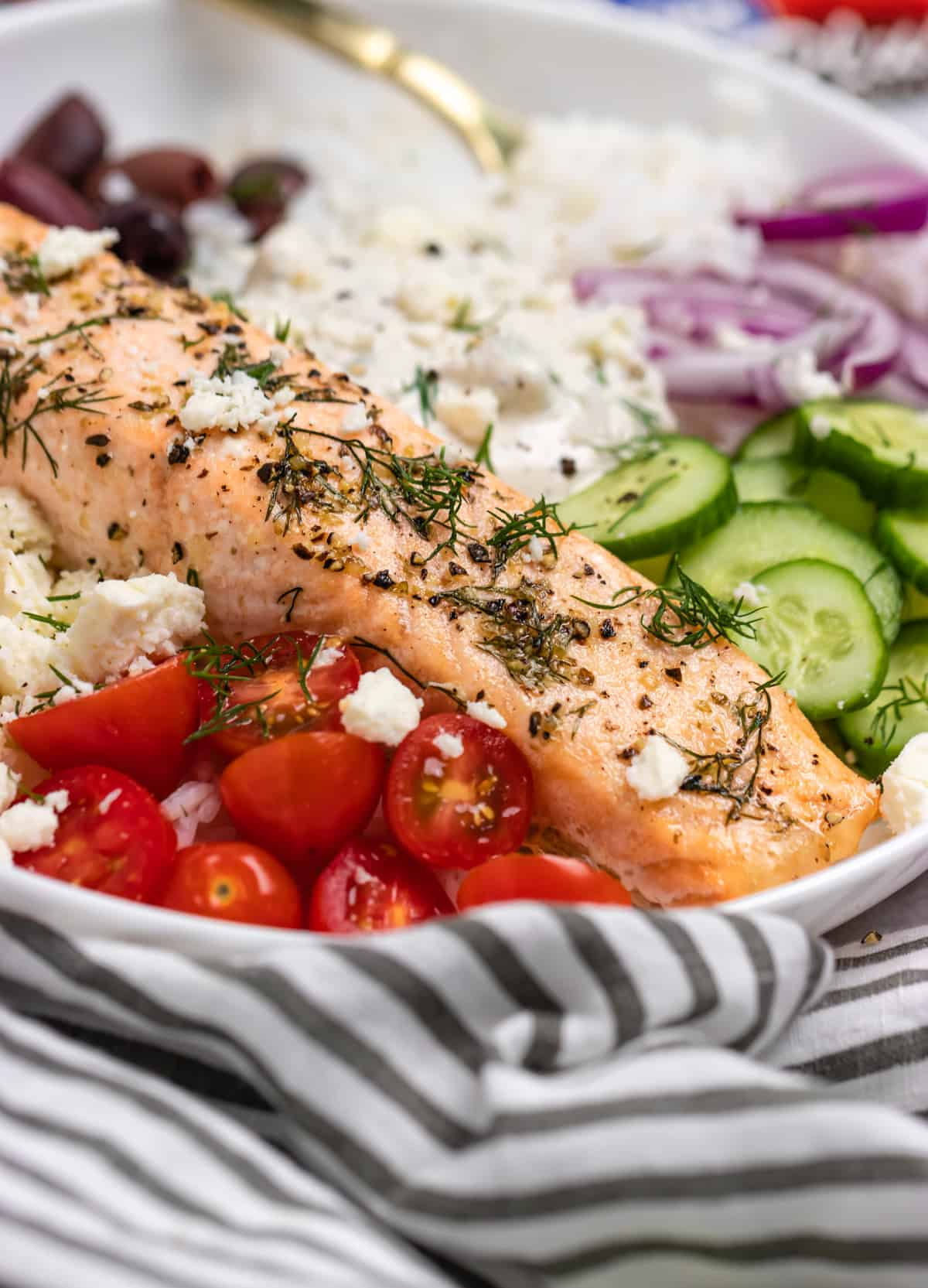 Salmon rice bowl with cucumber, onion, olives, rice and more.