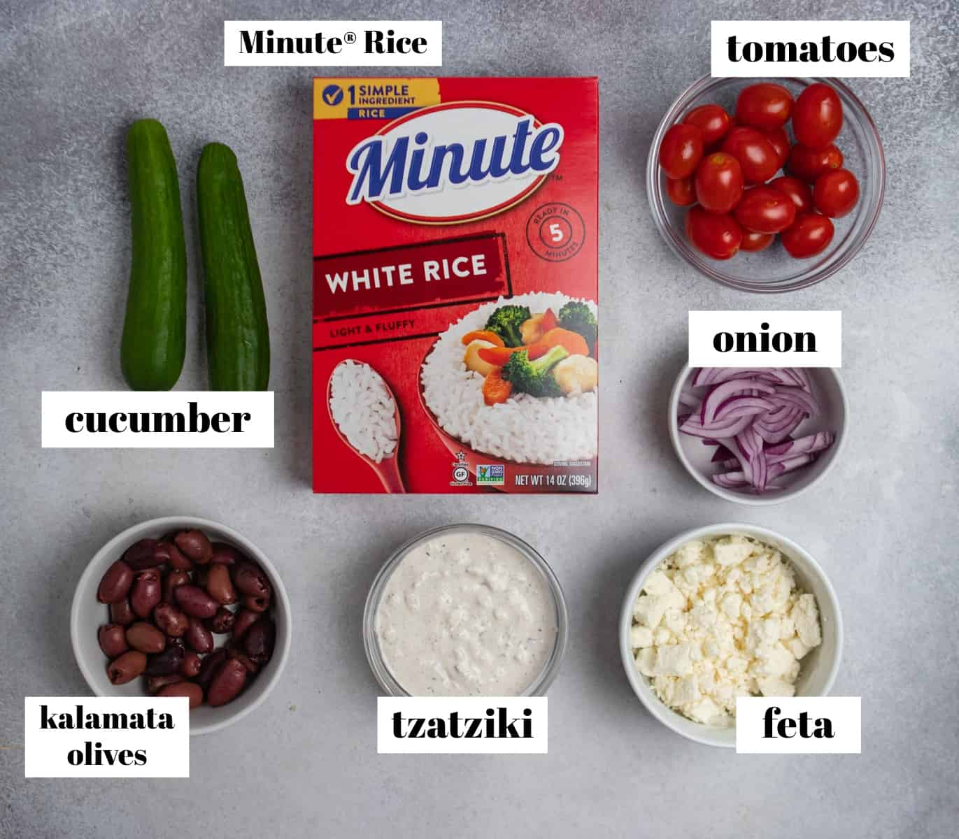 Rice, cucumbers, onion, feta, tzatziki and other ingredients labeled on counter.
