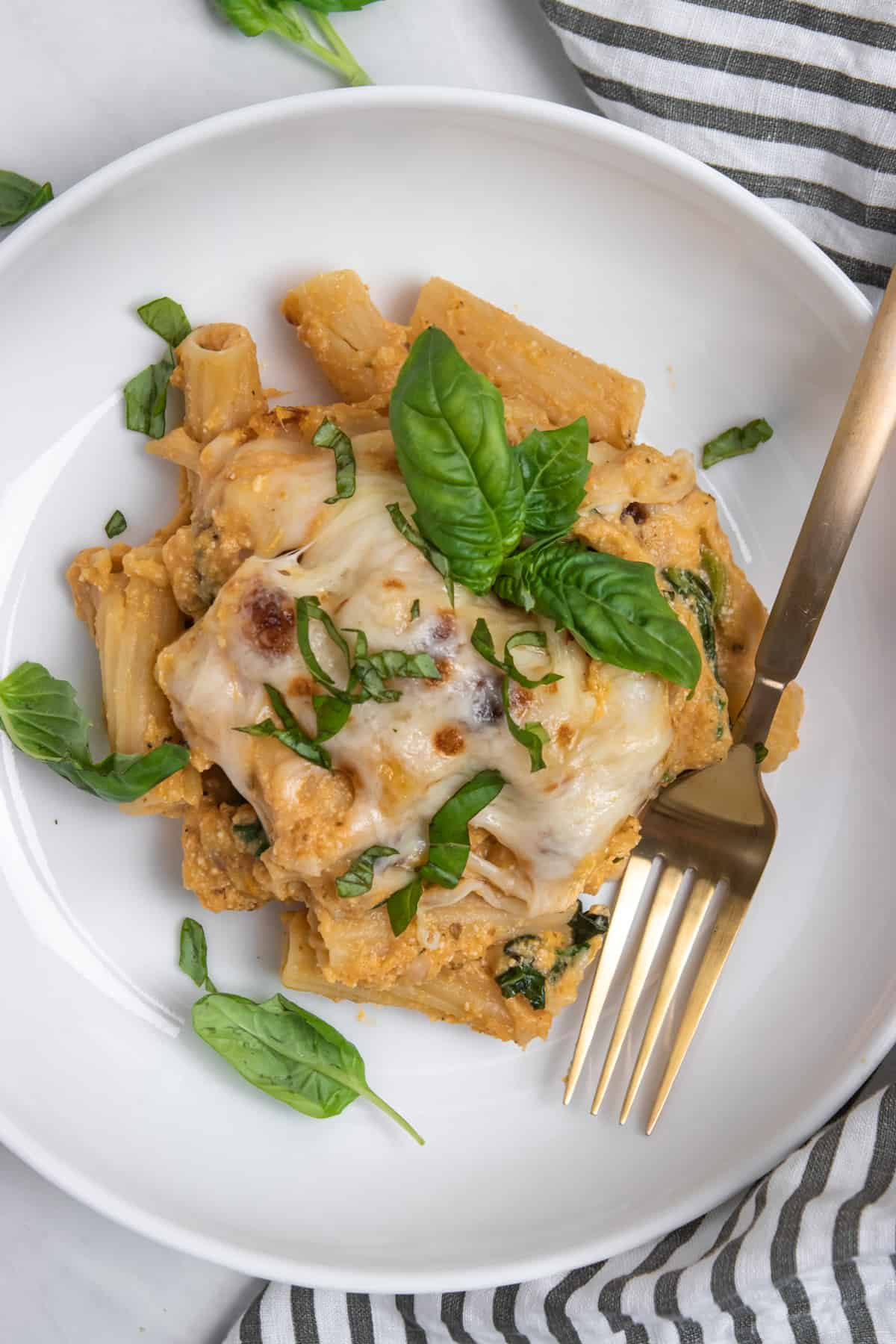 Overhead view of pumpkin pasta bake on white plate with fork and napkin.