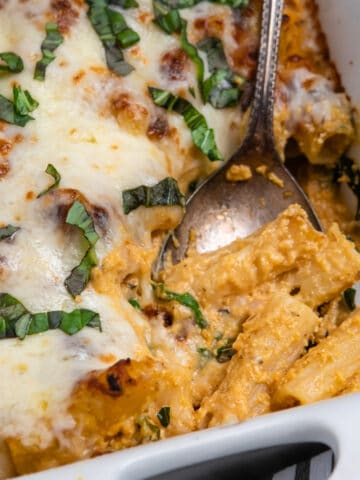 Spoon scooping out baked pumpkin rigatoni with fresh basil on top.
