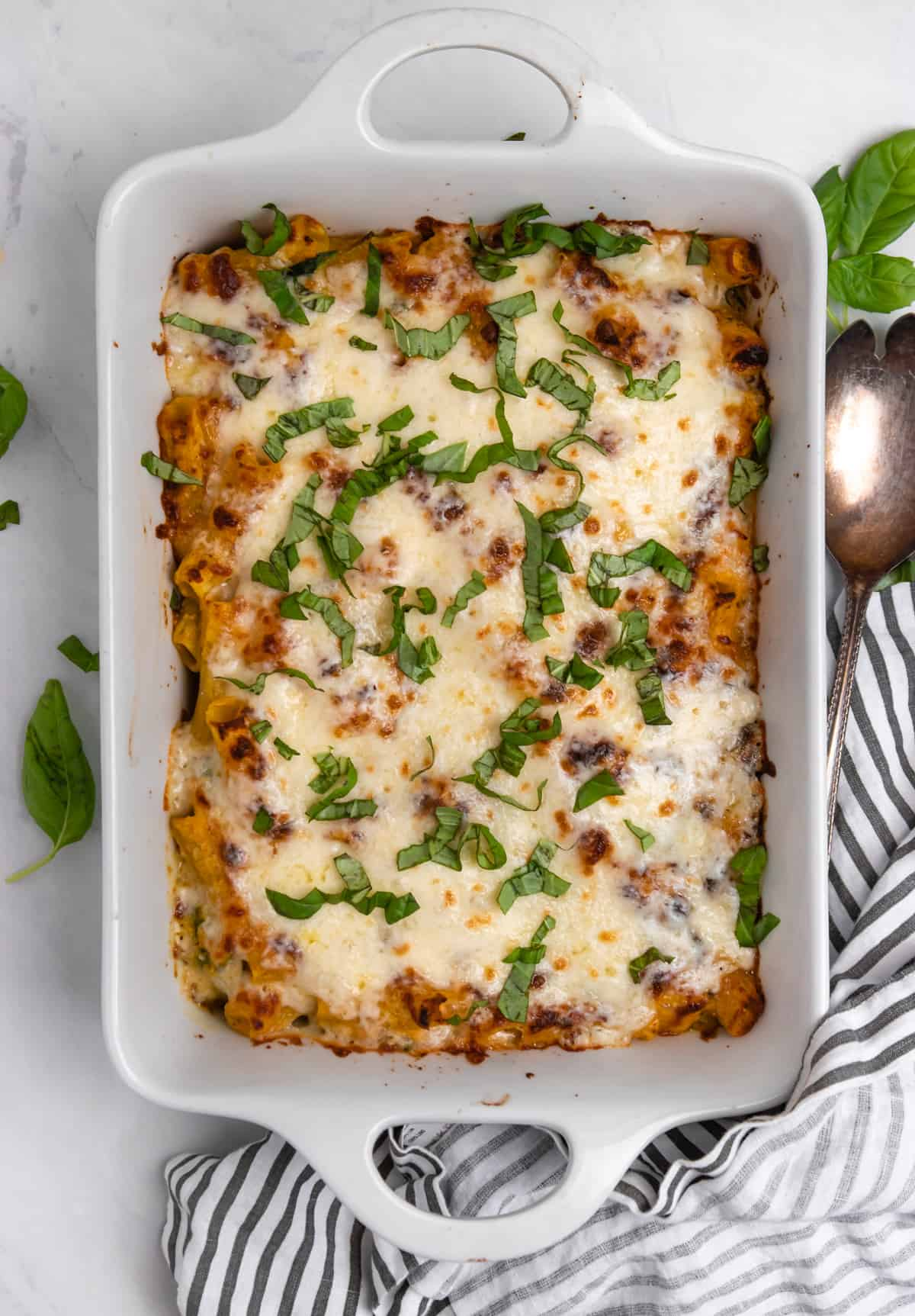 Overhead view of pumpkin pasta baked with ricotta and fresh basil on top.