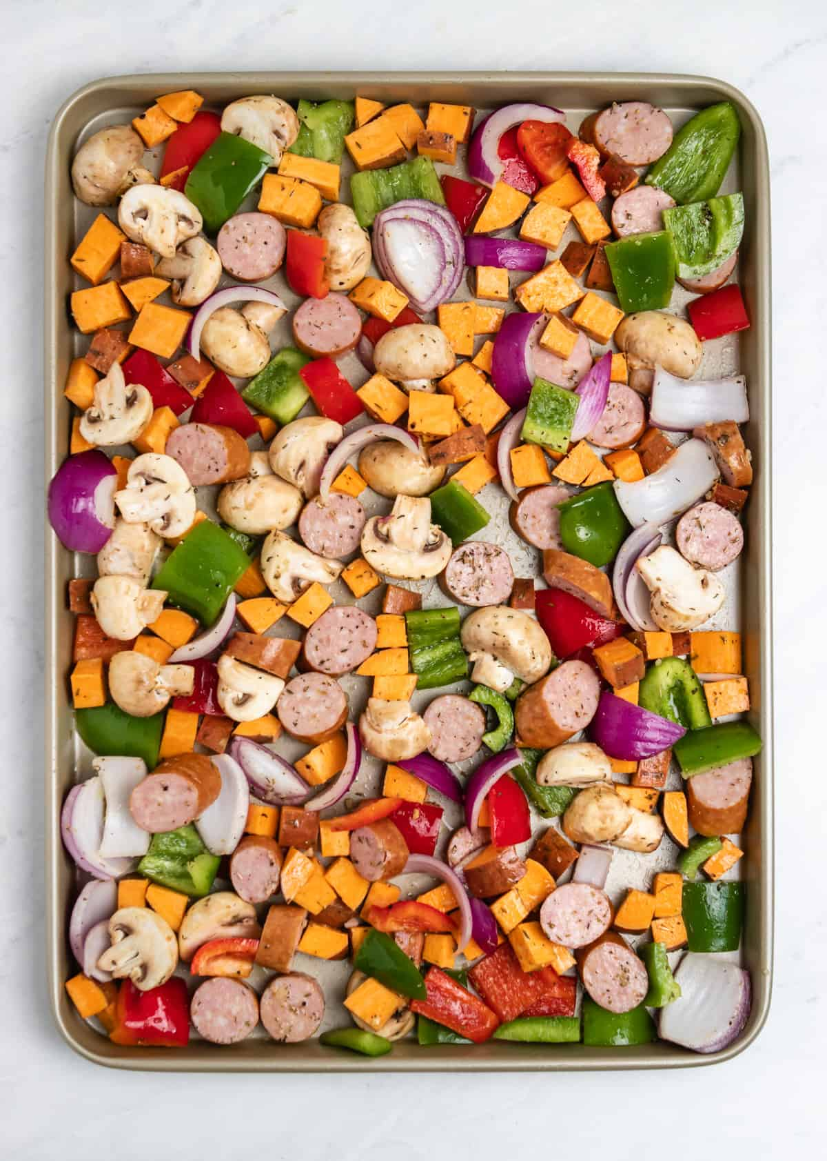 Veggies tossed in olive oil and spices on pan.