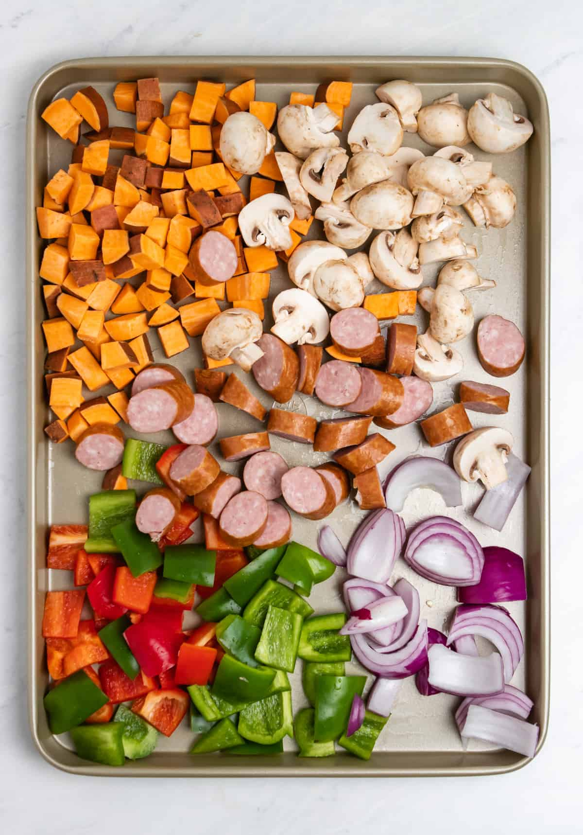 Fresh vegetables and sausages on sheet pan.