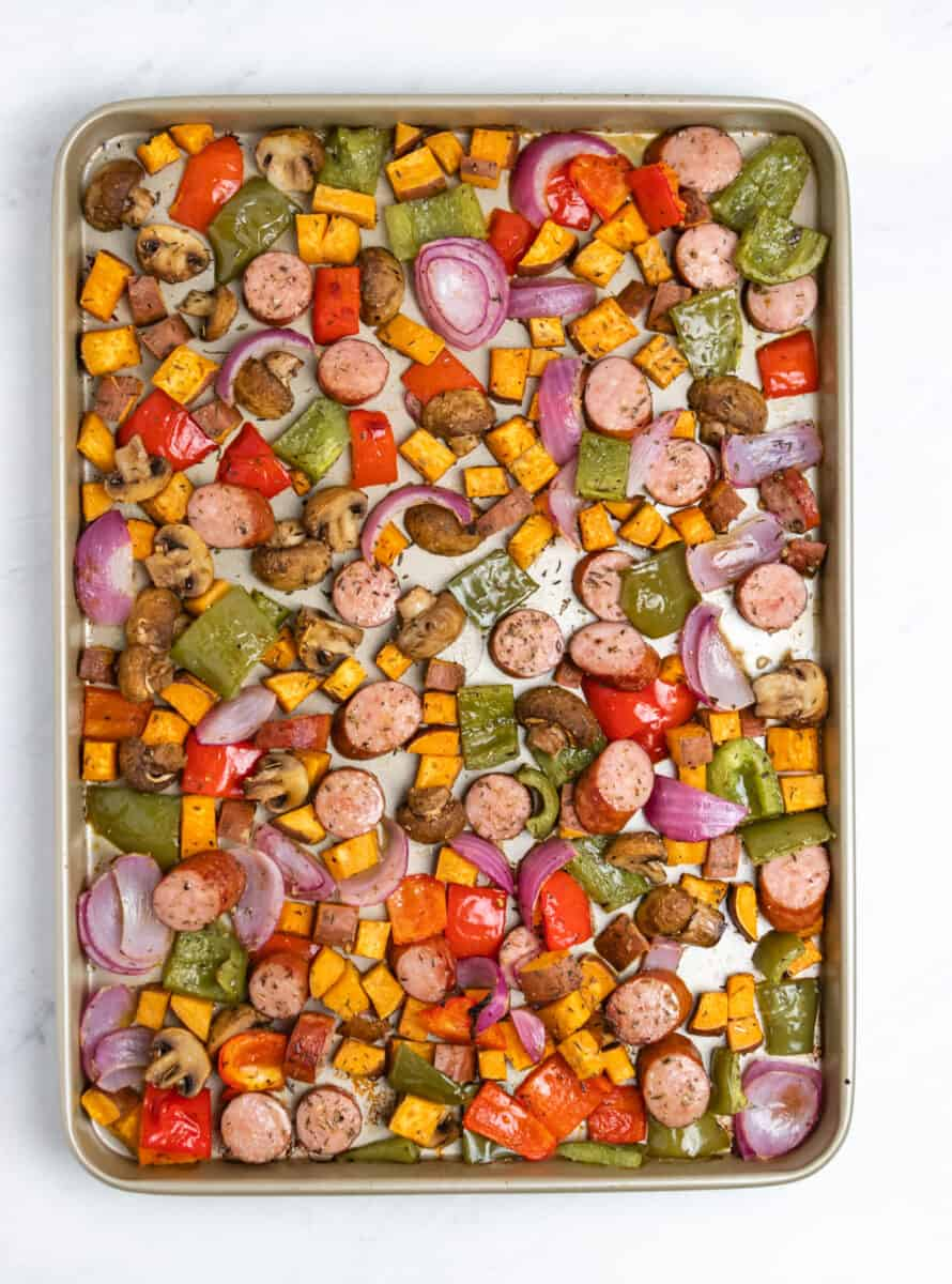 Kielbasa sausages, sweet potatoes, peppers and mushrooms cooked on a sheet pan.