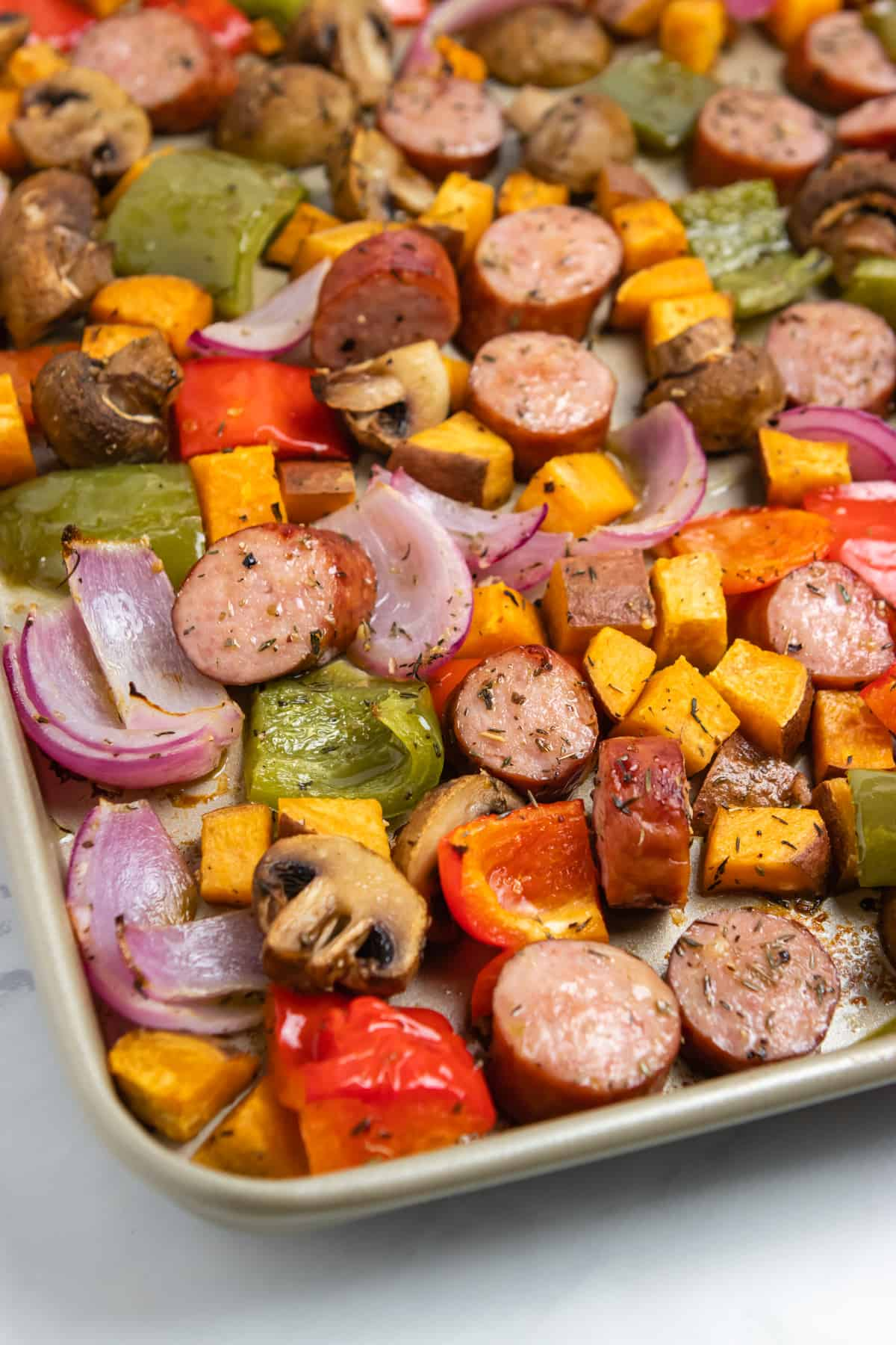 Sheet Pan with cooked sausages and vegetables.