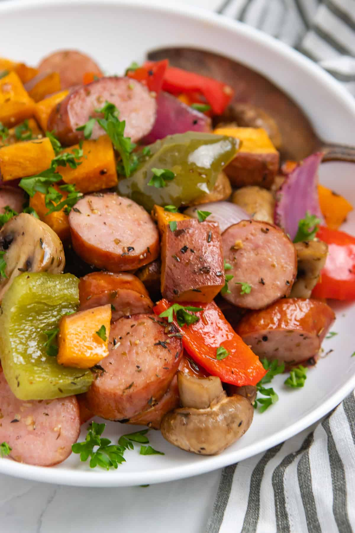 Bowl of cooked sausages, peppers and other veggies with spoon.
