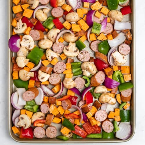 Sausages, sweet potatoes, peppers and mushrooms on pan before cooking.