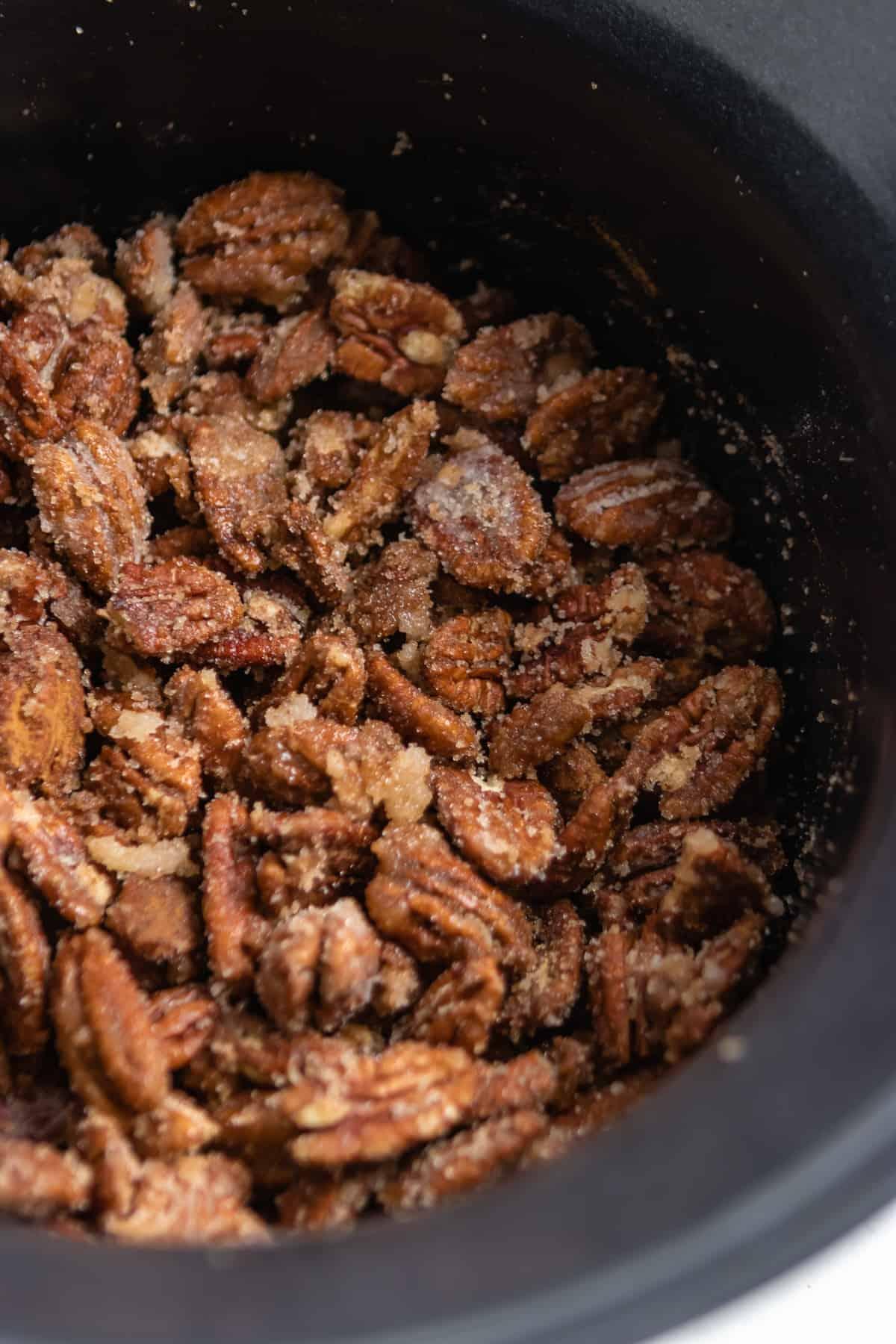 Cinnamon sugar coated pecans in slow cooker.