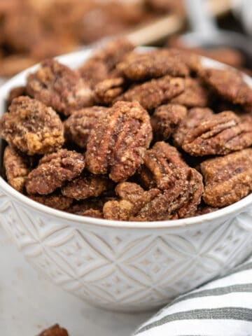 Bowl of candied pumpkin spiced pecans with striped linen and pan behind it.