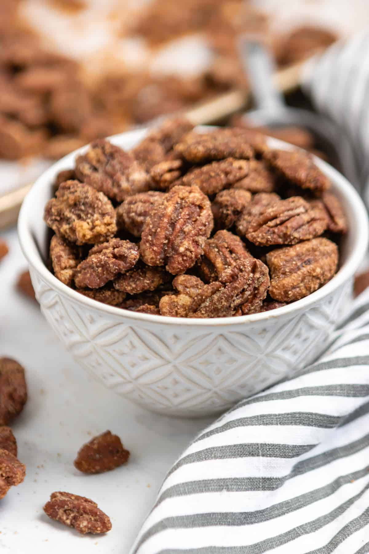 White bowl with candied pecans.
