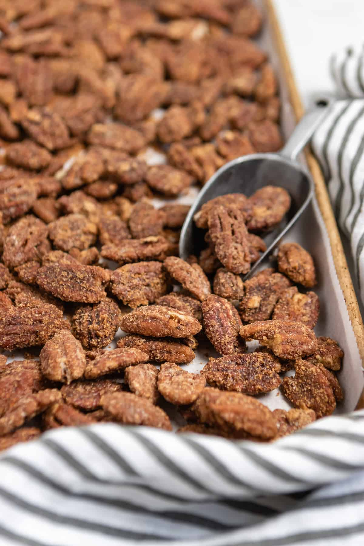 Sheet pan with pumpkin spiced cinnamon pecans and scoop.