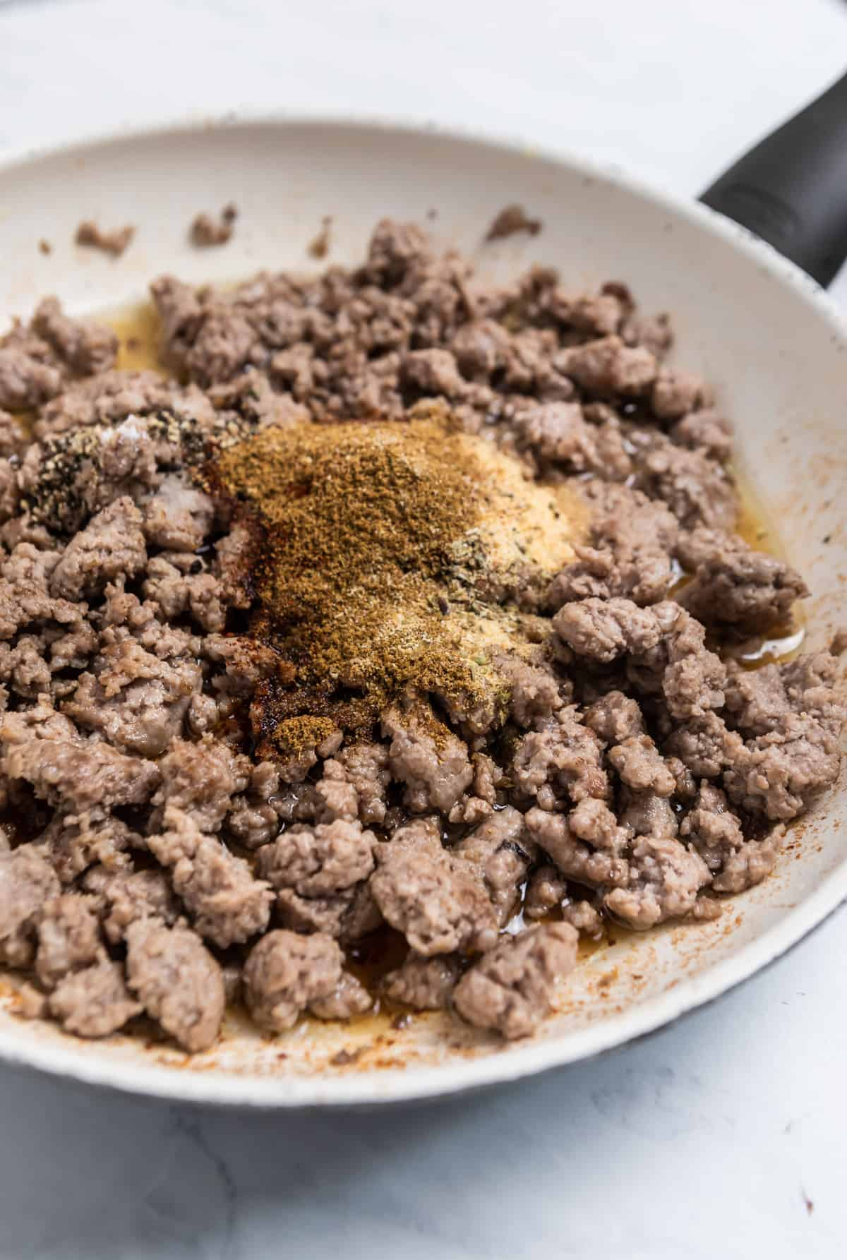 Browned ground pork in skillet with spices over top.