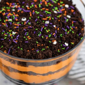 Trifle dish with layered Halloween dirt cake and Halloween sprinkles on top.