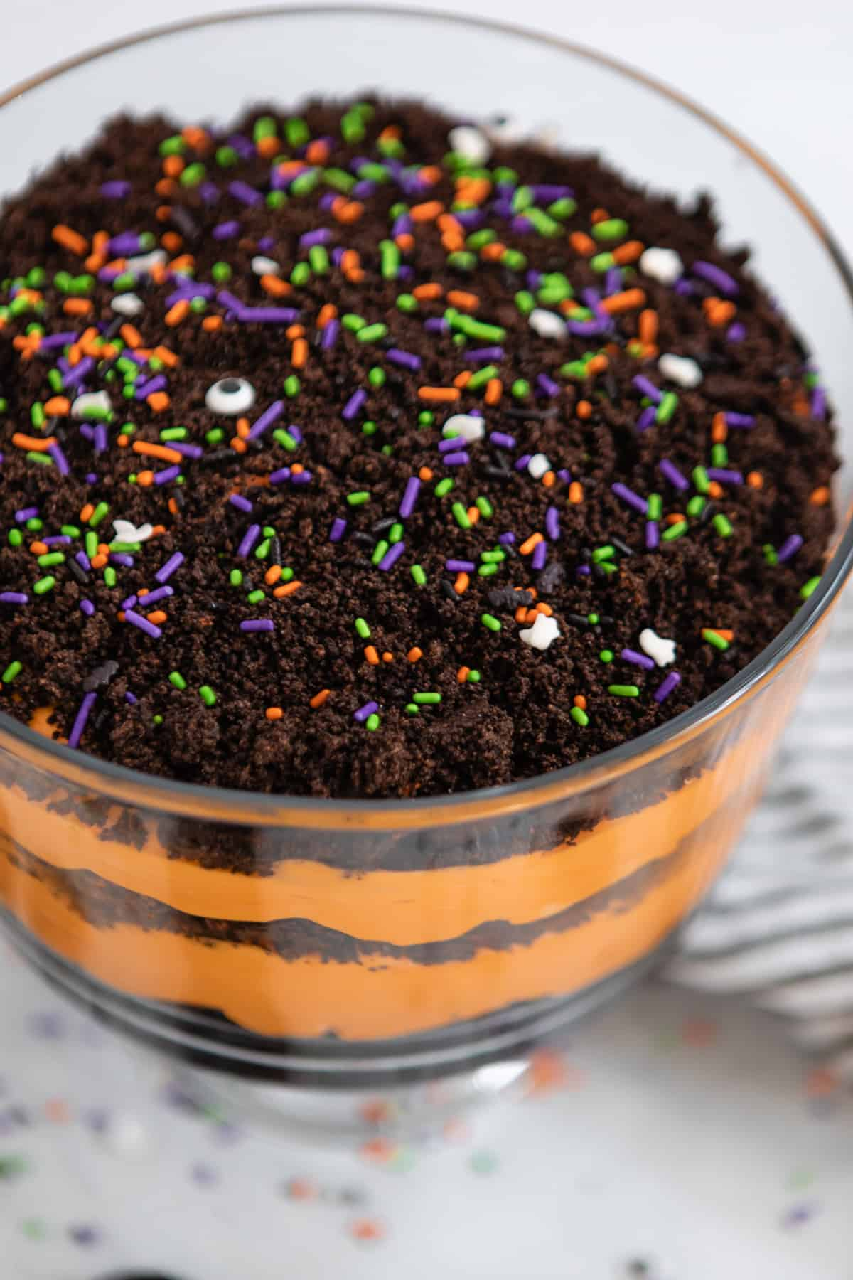 Trifle bowl with layered orange pudding and crushed Halloween Oreos.