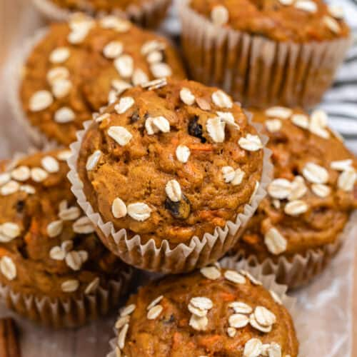 Pumpkin carrot muffins on wood tray with rolled oats on top.