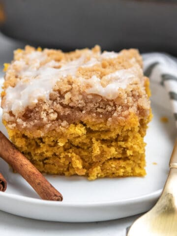 Slice of cinnamon streusel topped coffee cake with fork and cinnamon sticks on white plate.