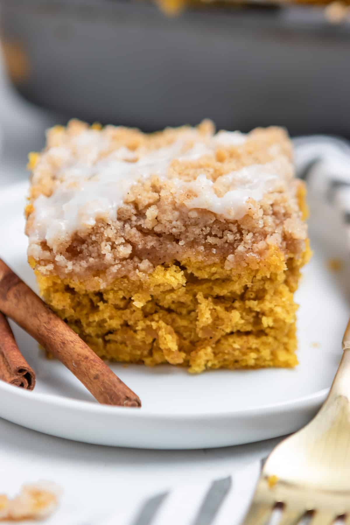 Pumpin coffee cake with streusel topping on white plate with cinnamon sticks.