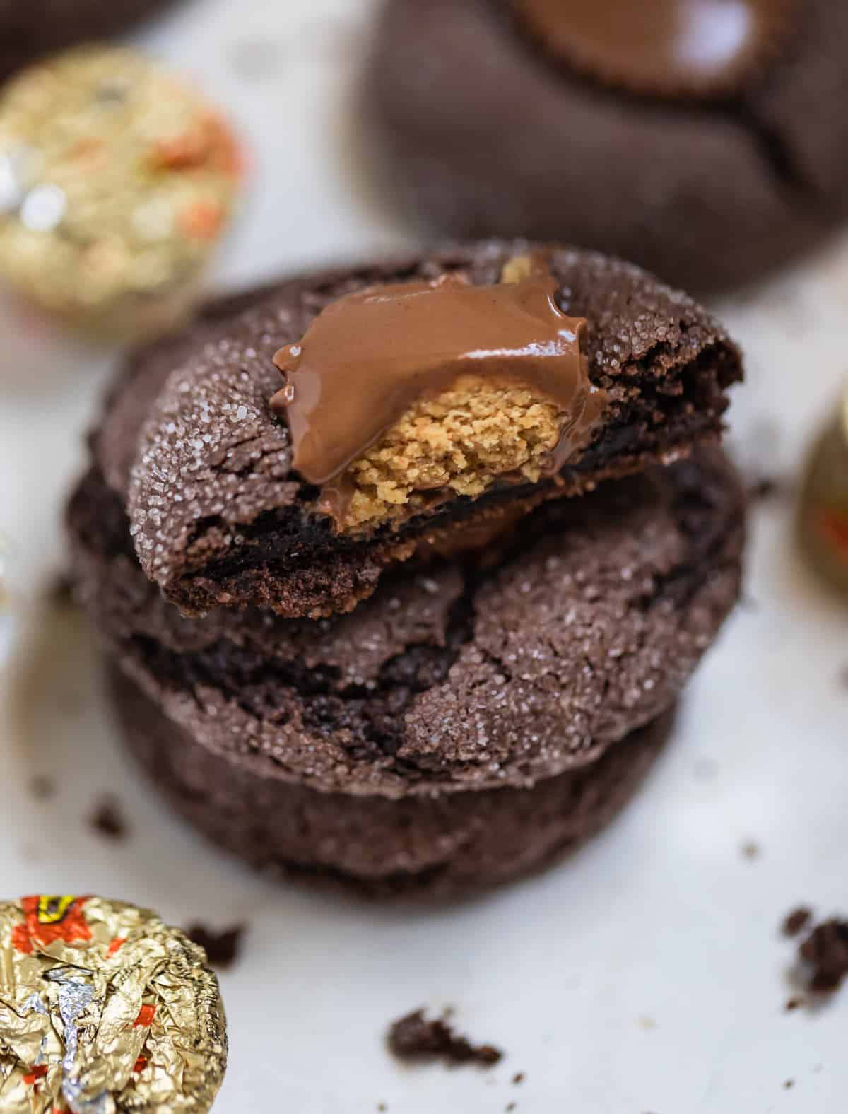 Chocolate cake mix cookie with Reese cup in center cut in half on stack of other cookies.