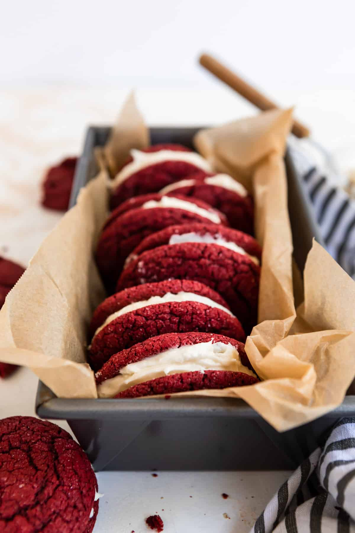 Red velvet cake mix sandwich cookies in bread pan lined with parchment.