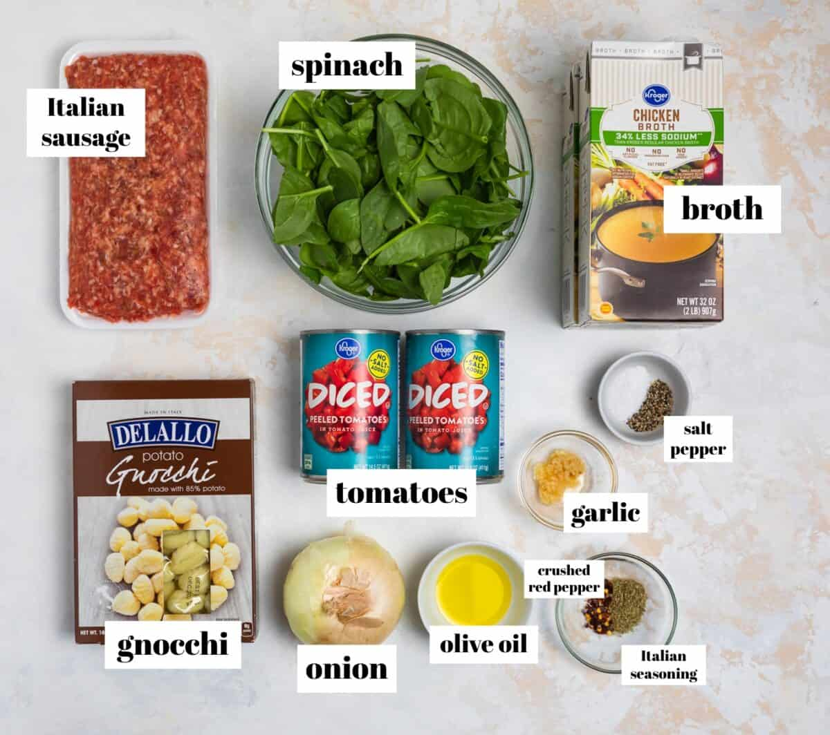 Broth, gnocchi, spinach, sausage and other ingredients labeled on counter.